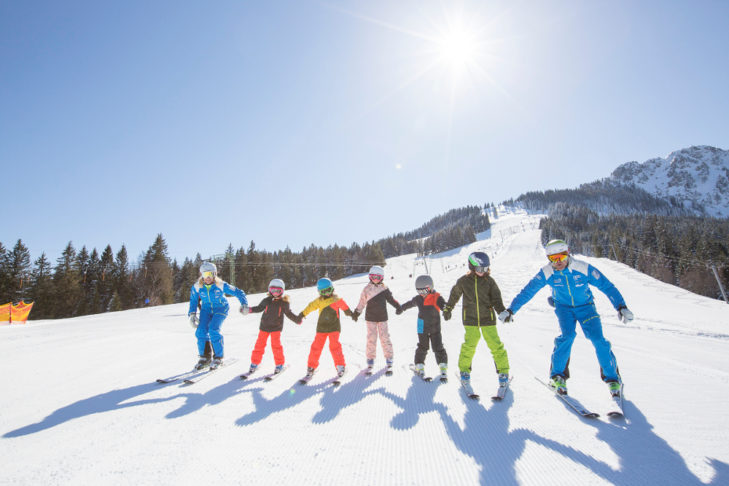 Children practice cautious skiing by holding hands, for example.