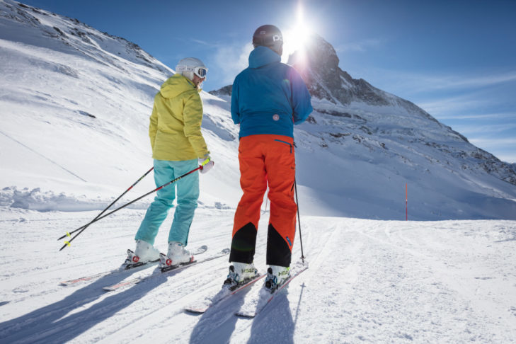 Sunshine skiing in front of the silhouette of Matterhorn in Zermatt.